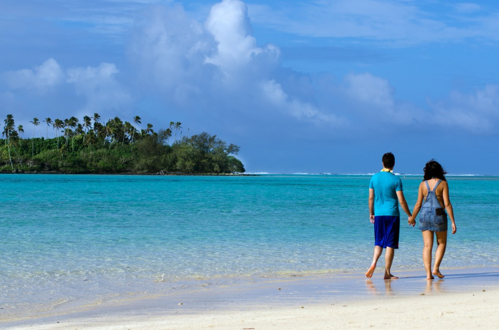 honeymoon couple walking on a beach in the South Pacific